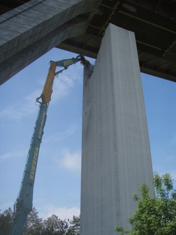 Strojní demolice odřezaného pilíře výškovým bagrem