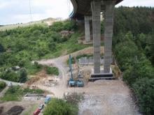 Výškový bagr s hydraulickými nůžkami připravený ke strojní demolici odřezaných pilířů